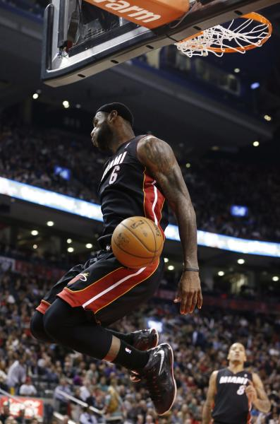 Miami Heat's LeBron James reacts after a slam dunk against the Toronto Raptors during the first half of an NBA basketball game in Toronto, Friday, Nov. 29, 2013. (AP Photo/The Canadian Press, Mark Blinch)