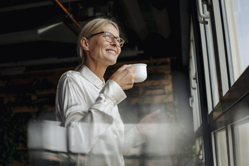 Smiling businesswomanholding cup of coffee looking out of window