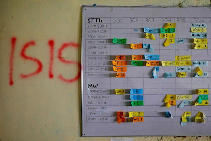 """A class schedule is seen on a wall spray-painted with """"ISIS"""" at a school in the most affected war-torn area of Marawi City, Lanao del Sur province, Philippines. (Photo: Eloisa Lopez/Reuters)"""
