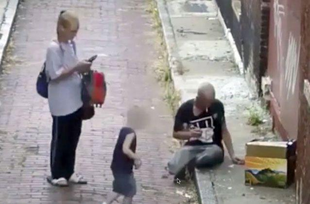 Unbelievable footage shows a mother injecting heroin in an alleyway with a man, while her son plays on a mobile phone nearby. Picture: Cincinnati Police Department