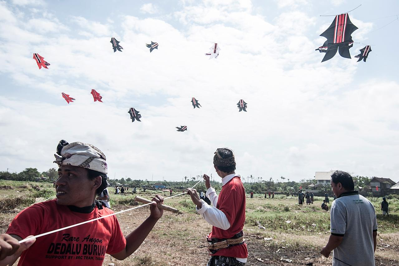 DENPASAR, BALI, INDONESIA - JULY 26: Participants pull the string to fly the traditional kites during the Bali Kite Festival on July 26, 2013 in Denpasar, Bali, Indonesia. The event is a seasonal religious festival, which is intended to send a message to Hindu Gods to create abundant harvests and crops. Aproximately 1121 traditional kites are flown during the three day annual Festival. (Photo by Putu Sayoga/Getty Images)