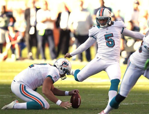Miami Dolphins kicker Dan Carpenter (5) aims at the ball as Miami Dolphins punter Brandon Fields (2) holds during the second half of an NFL football game against the Seattle Seahawks, Sunday, Nov. 25, 2012 in Miami. Carpenter's field goal won the game for the Dolphins 24-21. (AP Photo/Wilfredo Lee)