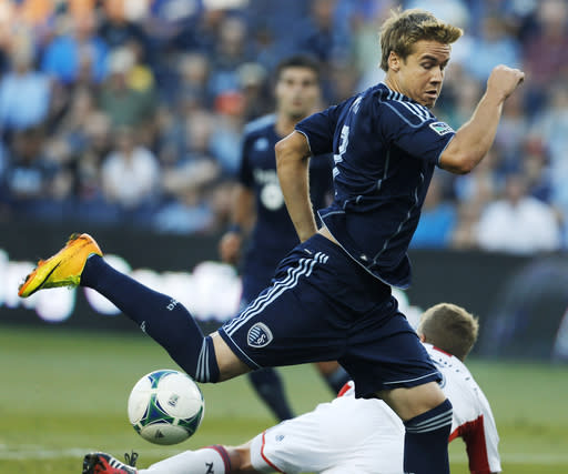 Sporting Kansas City defender Chance Myers, top, tries to get by New England Revolution midfielder Scott Caldwell during the first half of an MLS soccer match in Kansas City, Kan., Saturday, Aug. 10, 2013. (AP Photo/Orlin Wagner)