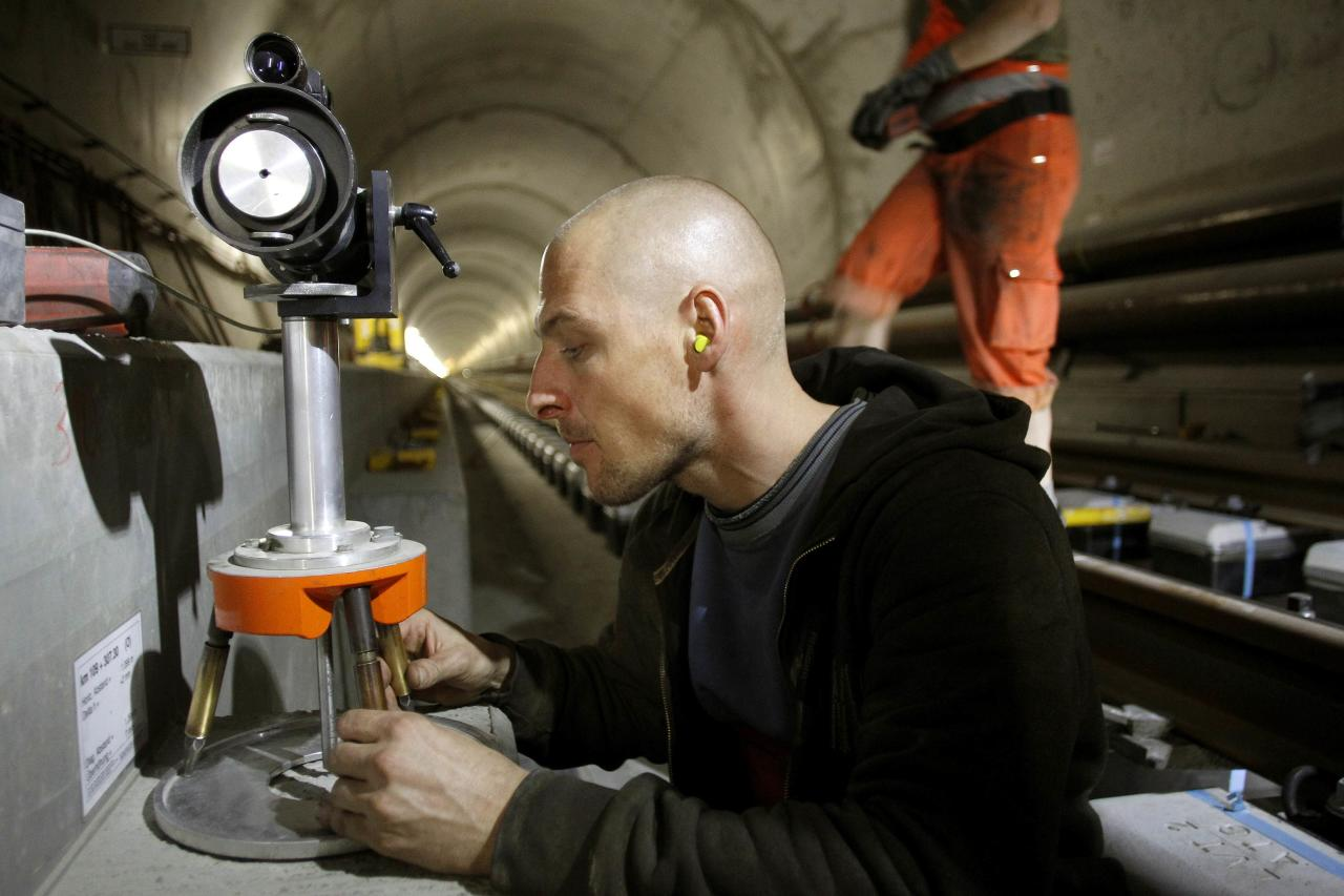 A worker adjusts a laser measuring gauge during the installation of the railway tracks in the NEAT Gotthard Base tunnel near Erstfeld May 7, 2012. Crossing the Alps, the world's longest train tunnel should become operational at the end of 2016. The project consists of two parallel single track tunnels, each of a length of 57 km (35 miles) REUTERS/Arnd Wiegmann   (SWITZERLAND - Tags: BUSINESS CONSTRUCTION EMPLOYMENT TRAVEL)