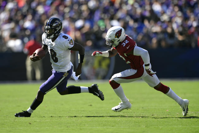 Baltimore Ravens quarterback Lamar Jackson, left, rushes past Arizona Cardinals strong safety Budda Baker in the second half of an NFL football game, Sunday, Sept. 15, 2019, in Baltimore. (AP Photo/Nick Wass)