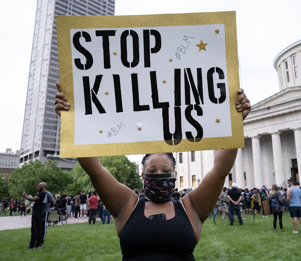 """A demonstrator holds a sign reading """"Stop Killing Us"""" in front of the Ohio Statehouse in Downtown Columbus, Ohio June 1, 2020 to peacefully protest the death of George Floyd. - Local US leaders appealed to citizens to give constructive outlet to their rage over the death of an unarmed black man in Minneapolis, while night-time curfews were imposed in cities including Washington, Los Angeles and Houston. (Photo by SETH HERALD / AFP) (Photo by SETH HERALD/AFP via Getty Images)"""