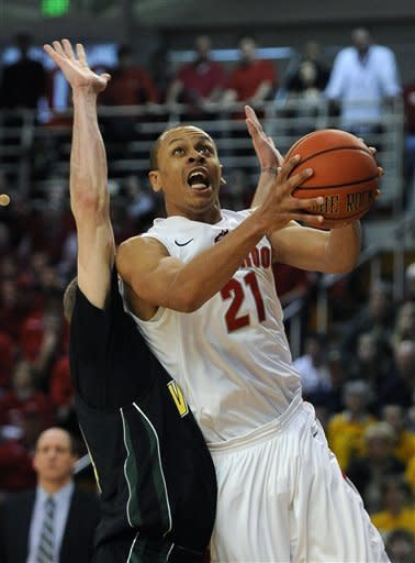 Stony Brook's Al Rapier (21) drives to the basket against Vermont's Matt Glass (34) during the first half of the America East Men's Basketball Championship game on Saturday, March 10, 2012, in Stony Brook, NY. (AP Photo/Kathy Kmonicek)