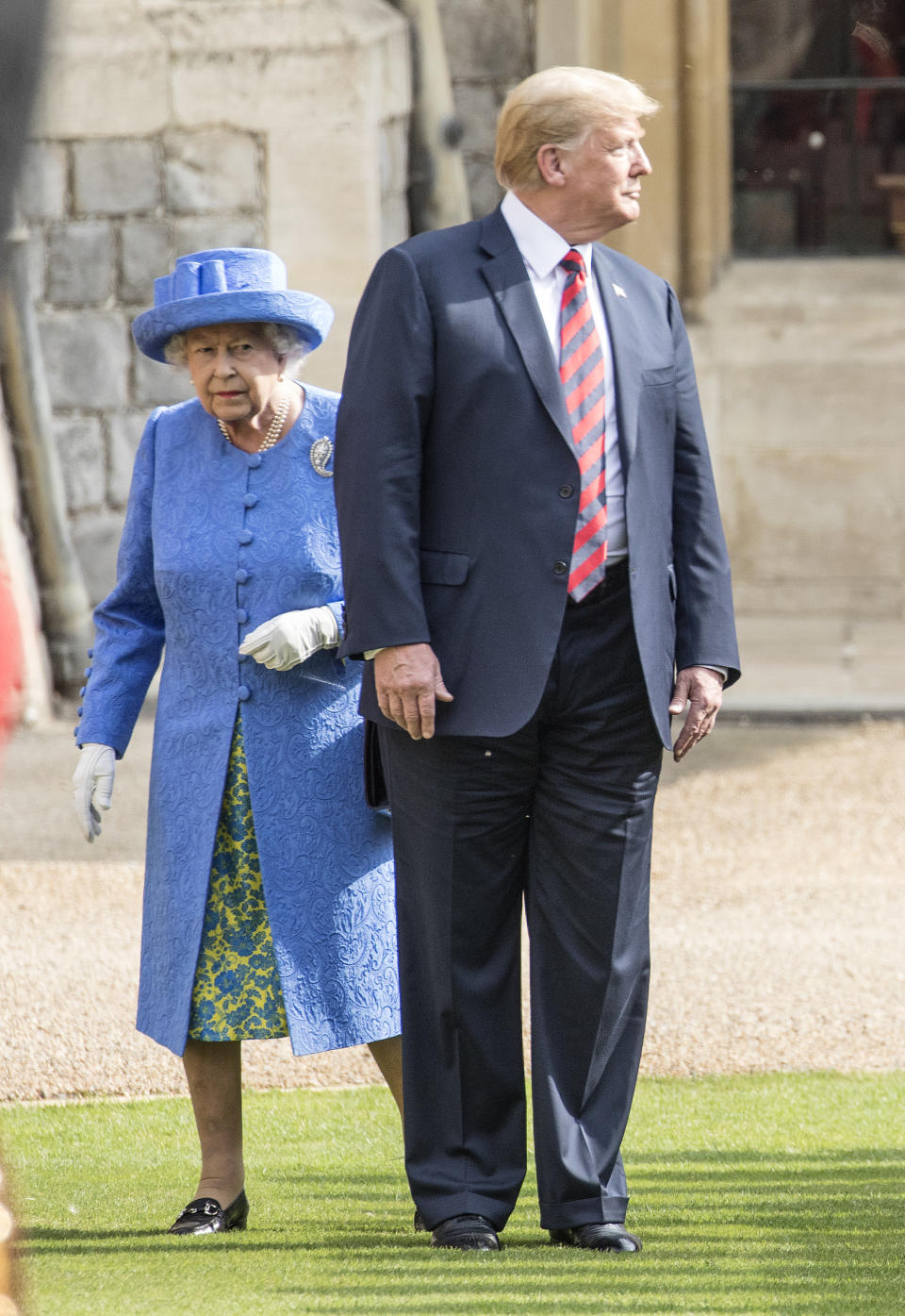 WINDSOR, ENGLAND - JULY 13: United States President Donald Trump and Britain's Queen Elizabeth II inspect a guard of honor formed by the Coldstream Guards at Windsor Castle on July 13, 2018 in Windsor, England.  Her Majesty greeted the President and Mrs. Trump on the podium in the square of the castle.  An honor guard, formed from the Coldstream Guards, gave a royal salute and the US national anthem was played.  The Queen and President inspected the honor guard before seeing the military march past.  The President and First Lady then joined Her Majesty for tea in the castle.  (Photo by Richard Pohle - WPA Pool / Getty Images)