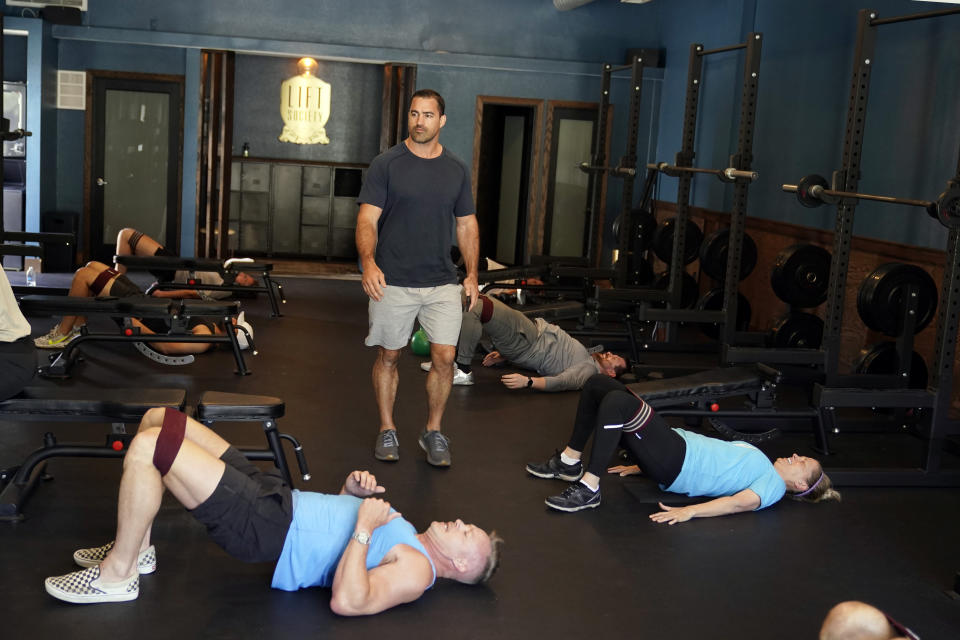 Owner David Schenk, standing, conducts a fitness class at Lift Society Friday, May 21, 2021, in Studio City, Calif. California's top health official says the state no longer will require social distancing and will allow full capacity for businesses when the state reopens on June 15. (AP Photo/Marcio Jose Sanchez)