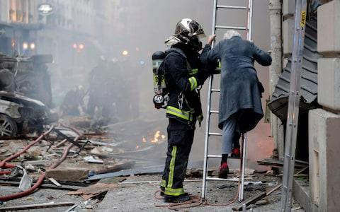 A woman is evacuated by firefighters after the explosion of a bakery on the corner of the streets Saint-Cecile and Rue de Trevise in central Paris - Credit: AFP