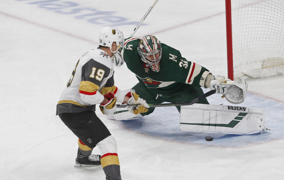 Minnesota Wild's Alex Stalock, right, stops a shot by Vegas Golden Knights' Reilly Smith in the first period of an NHL hockey game Tuesday, Feb. 11, 2020, in St. Paul, Minn. (AP Photo/Jim Mone)