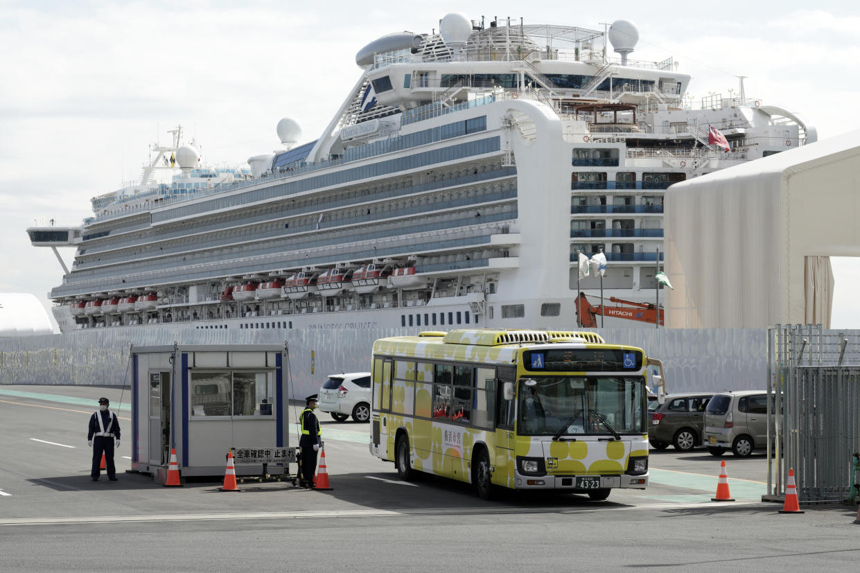 A bus carrying the passengers from the quarantined Diamond Princess cruise ship leaves a port in Yokohama, near Tokyo, Wednesday, Feb. 19, 2020. Passengers tested negative for COVID-19 started disembarking Wednesday. (AP Photo/Eugene Hoshiko)