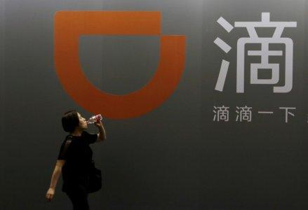 FILE PHOTO: A woman walks past Didi Chuxing's booth at the Global Mobile Internet Conference (GMIC) 2017 in Beijing, China April 28, 2017. REUTERS/Jason Lee/File Photo