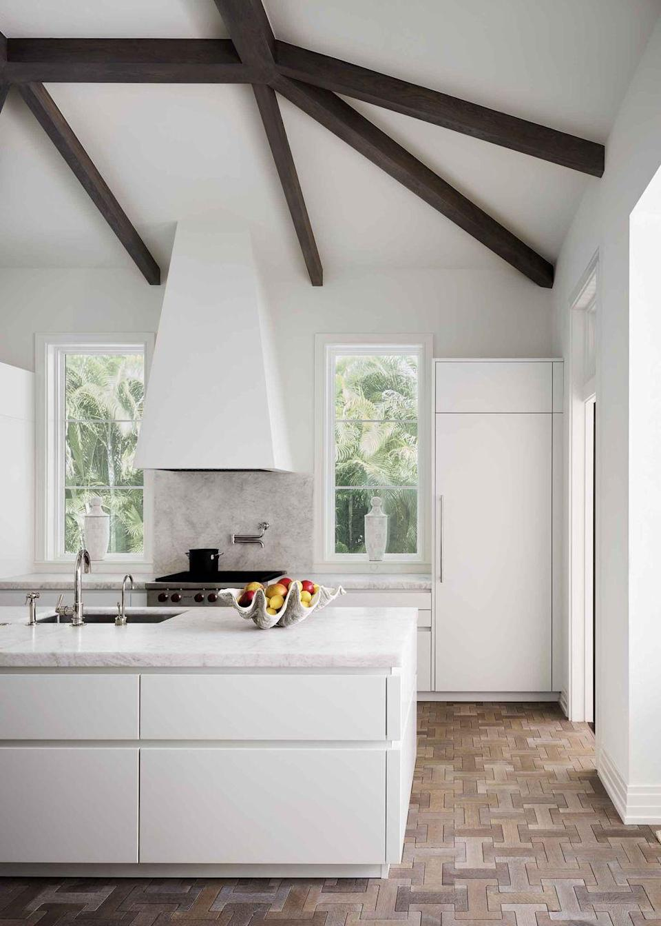 """<p>This serene foundation for this white kitchen in a <a href=""""https://www.veranda.com/home-decorators/a32166023/celerie-kemble-naples-florida-house-tour/"""" rel=""""nofollow noopener"""" target=""""_blank"""" data-ylk=""""slk:Naples, Florida, retreat"""" class=""""link rapid-noclick-resp"""">Naples, Florida, retreat</a> designed by <a href=""""http://www.kembleinteriors.com/"""" rel=""""nofollow noopener"""" target=""""_blank"""" data-ylk=""""slk:Celerie Kemble"""" class=""""link rapid-noclick-resp"""">Celerie Kemble</a> is its simple, unadorned cabinetry, which features drawer panels with no visible hardware. Dark-stained beams and interlocking white oak floor tiles from <a href=""""https://jamiebeckwithcollection.com/"""" rel=""""nofollow noopener"""" target=""""_blank"""" data-ylk=""""slk:Jamie Beckwith"""" class=""""link rapid-noclick-resp"""">Jamie Beckwith</a> add just a hint of rustic warmth.</p>"""