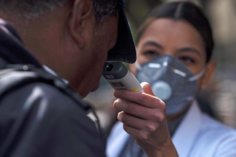 A nurse checks a man's temperature at the entrance of Tijuana's General Hospital, in Tijuana, Mexico, on March 2, 2020. - Mexico confirmed its fourth case of the new coronavirus on Saturday, February 29, 2020, after a young woman tested positive for infection. (Photo by Guillermo Arias / AFP) (Photo by GUILLERMO ARIAS/AFP via Getty Images)