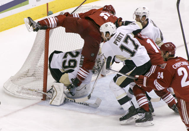 Phoenix Coyotes' Connor Murphy (5) collides with Pittsburgh Penguins goaltender Marc-Andre Fleury (29) as Penguins' Taylor Pyatt (17) and Brooks Orpik, second from right, chase down the puck ahead of Coyotes' Jeff Halpern (14) and Kyle Chipchura (24) during the second period of an NHL hockey game on Saturday, Feb. 1, 2014, in Glendale, Ariz. (AP Photo/Ralph Freso)