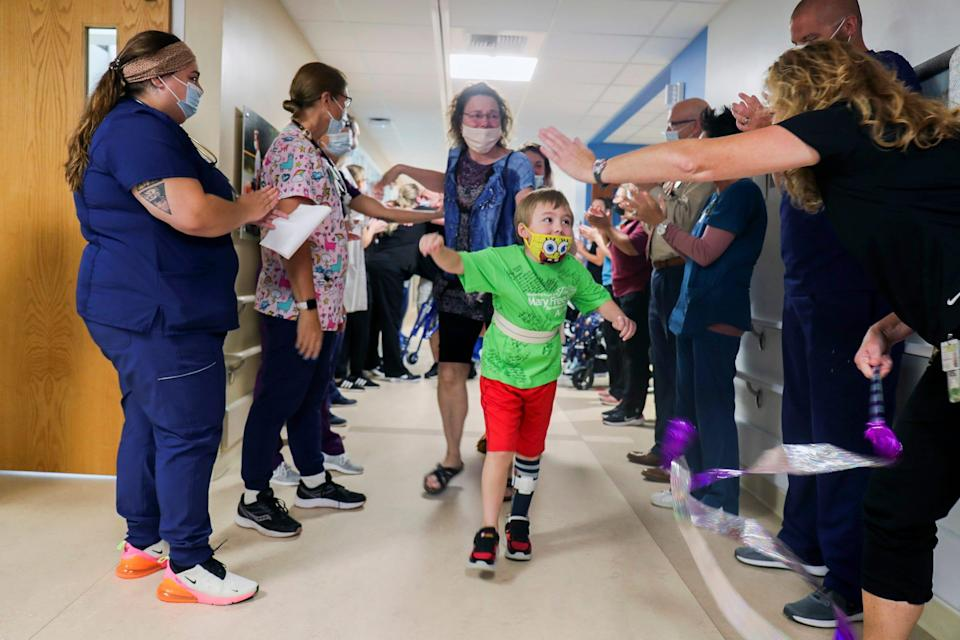 Waylon Wehrle, 7, had COVID-19 in the spring and developed life-threatening complications. He suffered multiple strokes and myocarditis. The staff claps as Waylon leaves the Mary Free Bed Rehabilitation Hospital in Grand Rapids after two months.
