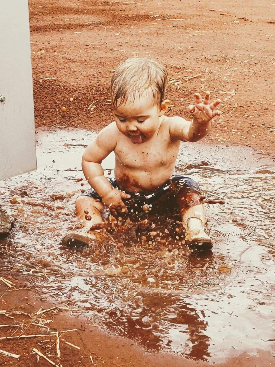 Lacey is pictured sitting in a puddle while splashing the water with her hands. Source: Emma Sewell