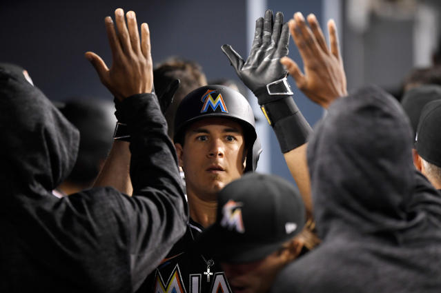 Miami Marlins' J.T. Realmuto is congratulated by teammates after hitting a solo home run during the third inning of the team's baseball game against the Los Angeles Dodgers on Tuesday, April 24, 2018, in Los Angeles. (AP Photo/Mark J. Terrill)