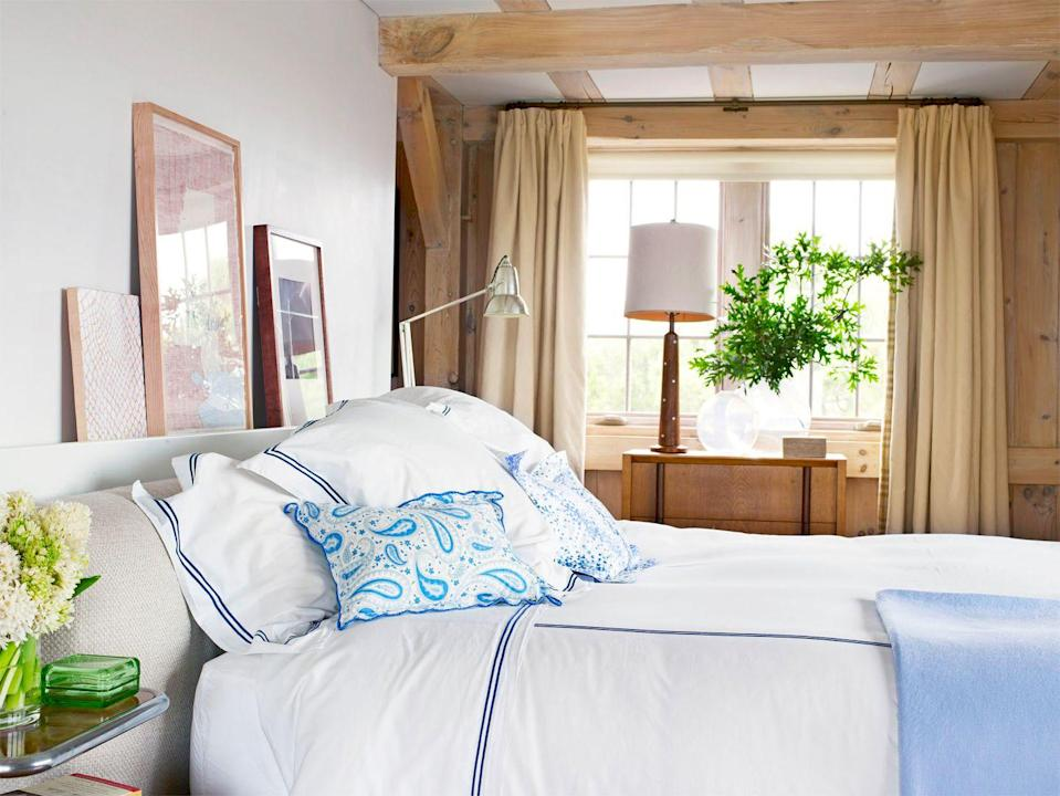 <p>Exposed beams in this country home bedroom are brightened up by the crisp blue-and-white bedding and silver table lamp. The mix of warm and cool tones balance each other out well and prove that wood ceilings don't have to look bohemian or rustic—they can be preppy and prim, too.</p>