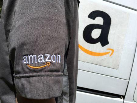 FILE PHOTO: An Amazon.com Inc driver stands next to an Amazon delivery truck in Los Angeles, California
