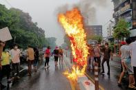 Anti-coup protesters burn a Chinese flag in Yangon