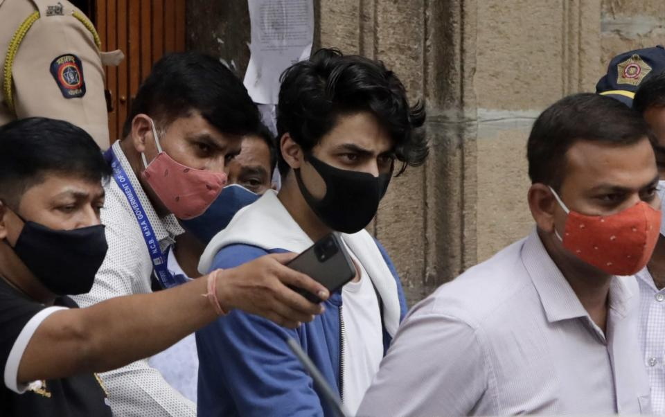 Bollywood actor Shah Rukh Khan's son Aryan Khan, center, escorted by law enforcement officials from Narcotics Control Bureau office is being taken for a medical check up, in Mumbai, India, Friday, Oct. 08, 2021.(AP Photo/Rajanish kakade)
