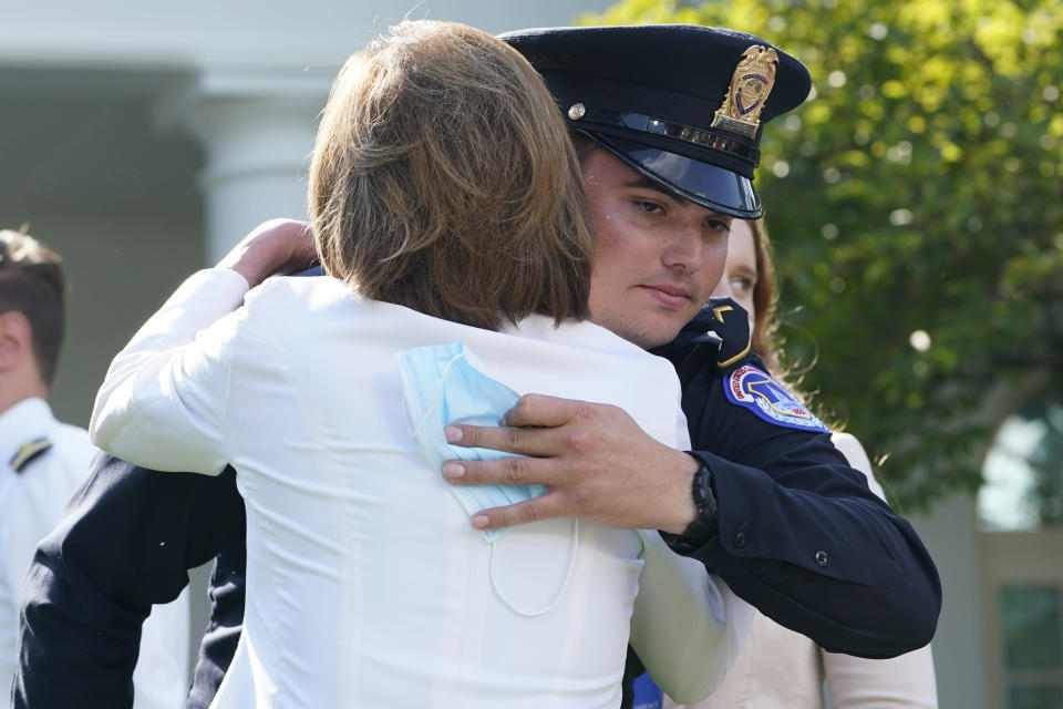House Speaker Nancy Pelosi of Calif., hugs a U.S. Capitol Police officer before President Joe Biden signs a bill in the Rose Garden of the White House, in Washington, Thursday, Aug. 5, 2021, that awards Congressional gold medals to law enforcement officers that protected members of Congress at the Capitol during the Jan. 6 riot. (AP Photo/Susan Walsh)