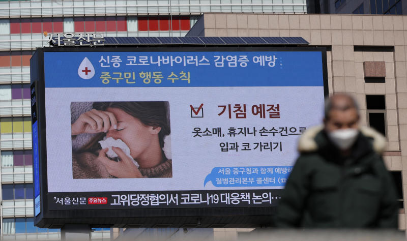 "A huge screen about precautions against the COVID-19 is seen in downtown Seoul, South Korea, Sunday, Feb. 23, 2020. South Korea and China both reported a rise in new virus cases on Sunday, as the South Korean prime minister warned that the fast-spreading outbreak linked to a local church and a hospital in the country's southeast had entered a ""more grave stage."" The screen reads ""Cough etiquette."" (AP Photo/Lee Jin-man)"