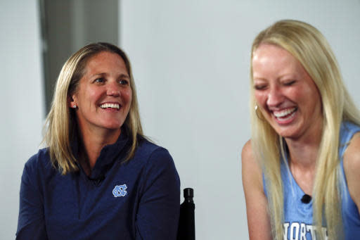 FILE - In this Oct. 3, 2019, file photo, North Carolina women's basketball coach Courtney Banghart, left, laughs with guard Taylor Koenen during the Atlantic Coast Conference women's NCAA college basketball media day in Charlotte, N.C. Banghart is taking over a North Carolina program in need of an overhaul on and off the court.(AP Photo/Nell Redmond, File)