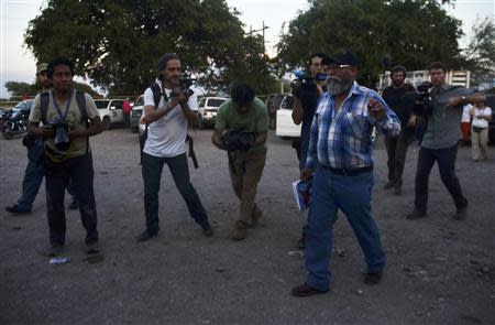 Estanislao Beltran, spokesperson for the vigilantes, walks past photographers and camera operators in Tecapaltepec