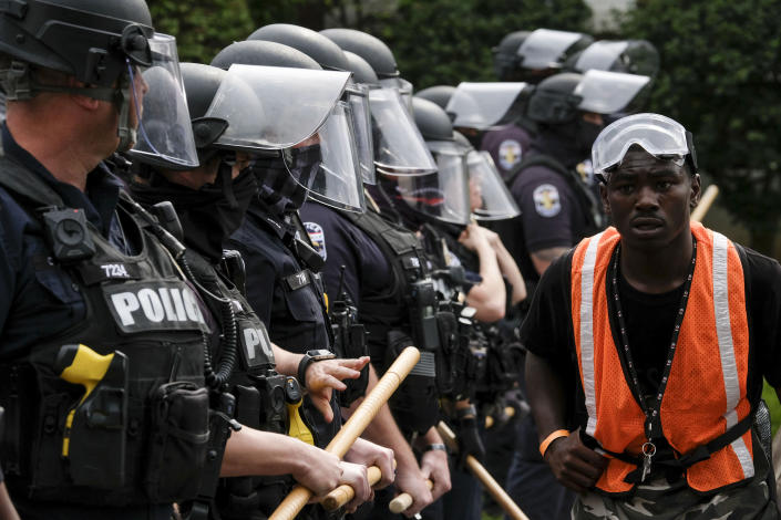 A protester marches by a police line in downtown Louisville on Sept. 23. (Jeff Dean/AFP via Getty Images)