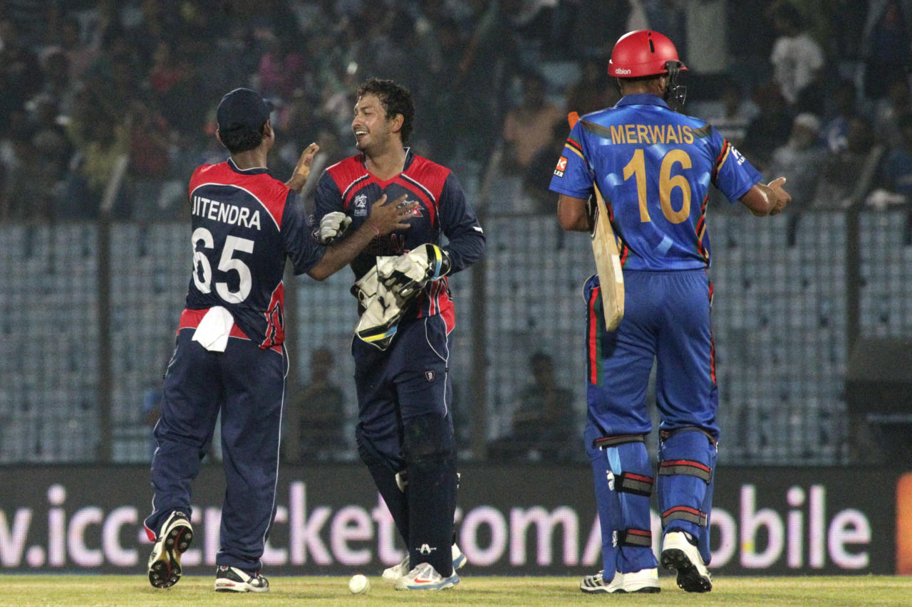Nepal's Subash Khakurel, second right, and Jitendra Mukhiya celebrate after defeating Afghanistan by nine runs during their ICC Twenty20 Cricket World Cup match in Chittagong, Bangladesh, Thursday, March 20, 2014. Afghanistan's Mirwais Ashraf at right. (AP Photo/Bikas Das)