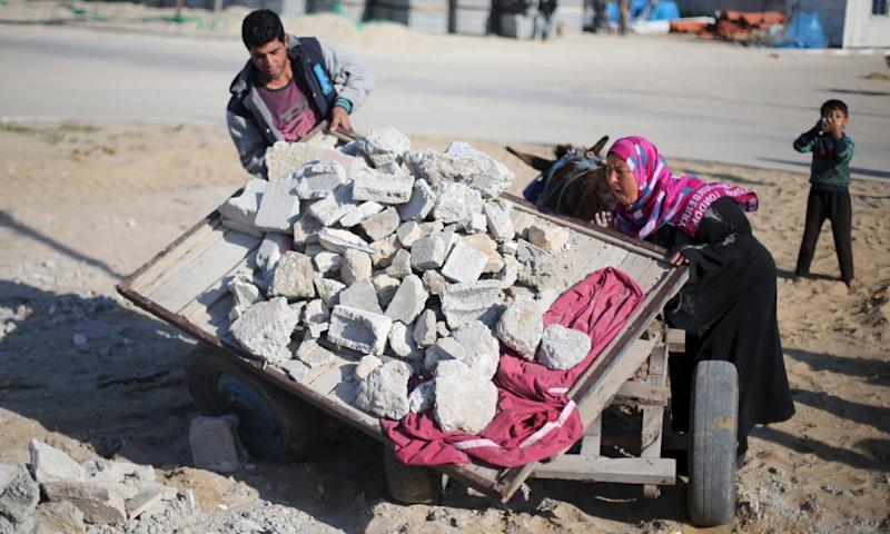 A Palestinian woman unloads a cart of concrete rubble she has collected from bomb sites.