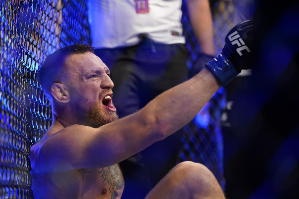 Conor McGregor yells as he sits on the mat after an injury during his lightweight mixed martial arts bout with Dustin Poirier at UFC 264 on Saturday, July 10, 2021, in Las Vegas. (AP Photo/John Locher)