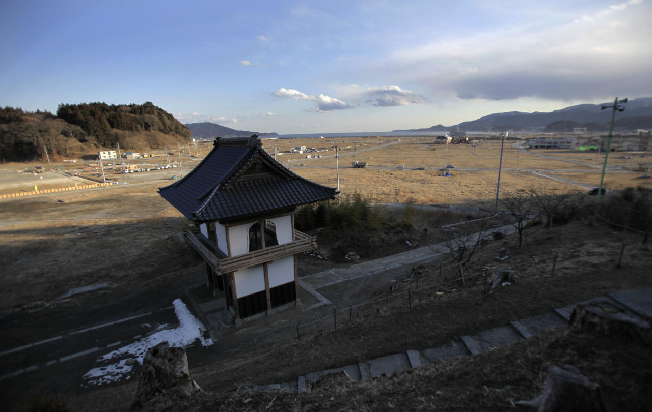In this Friday, Feb. 22, 2013 photo, a temple gate stands in an area devastated by the March 11, 2011 earthquake and tsunami in Rikuzentakata, Iwate Prefecture. Japan's progress in rebuilding from the tsunami that thundered over coastal sea walls, sweeping entire communities away, is mainly measured in barren foundations and empty spaces. Clearing of forests on higher ground due to be leveled to make space for relocating survivors has barely begun. Japan will next week observes two years from the March 11, 2011 disasters which devastated in the northeastern Pacific coast of the country. (AP Photo/Junji Kurokawa)