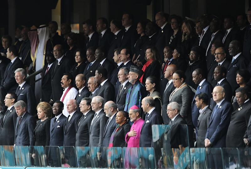 VIP's and dignitaries stand up for the start of the memorial service for former South African president Nelson Mandela at the FNB Stadium in Soweto, near Johannesburg, South Africa, Tuesday Dec. 10, 2013. (AP Photo/Peter Dejong)