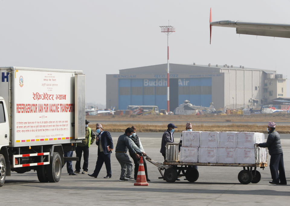 FILE - In this Jan. 21, 2021, file photo, Nepalese airport ground staffs pull a trolly full of boxes containing AstraZeneca/Oxford University vaccine, manufactured under license by Serum Institute of India, arrive at Tribhuwan International Airport in Kathmandu, Nepal. As the coronavirus pandemic exploded worldwide last April, global organizations banded together to help ensure vaccines would be distributed fairly. But the COVAX initiative has been dogged by shortages of cash and supplies as well as logistical hurdles. Some poorer countries have been unwilling to wait for COVAX, and have found other ways to get vaccines. (AP Photo/Niranjan Shrestha, File)