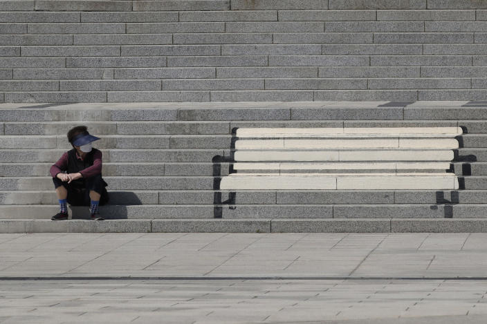 A woman wearing a face mask takes a look at stairs on which a bench is painted in Goyang, South Korea, Friday, April 9, 2021. (AP Photo/Lee Jin-man)
