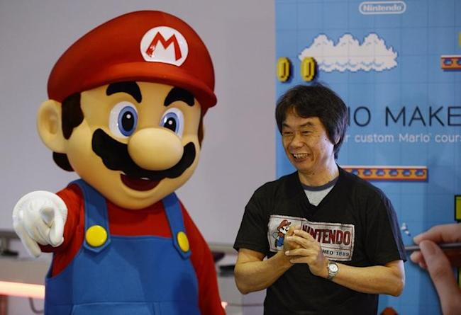 Shigeru Miyamoto, senior managing director of Nintendo and general manager of its Entertainment Analysis and Development division, together with Nintendo character Mario (L), introduces the new game