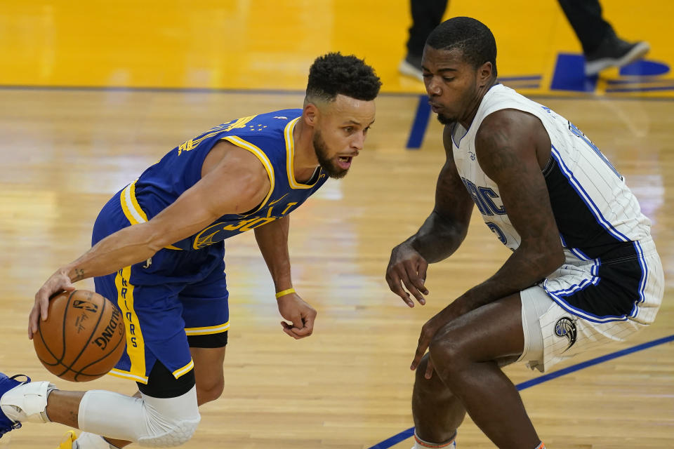 Golden State Warriors guard Stephen Curry, left, dribbles against Orlando Magic forward Gary Clark during the first half of an NBA basketball game in San Francisco, Thursday, Feb. 11, 2021. (AP Photo/Jeff Chiu)