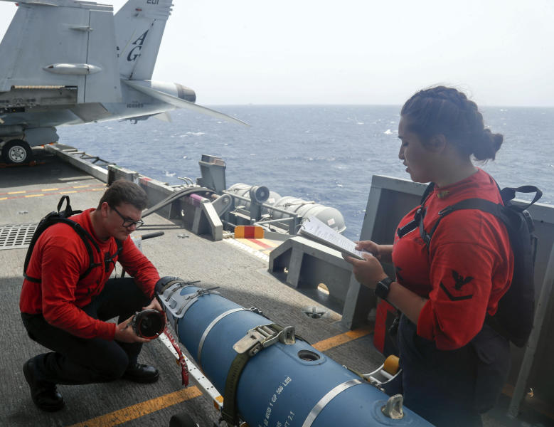 "In this Wednesday, May 15, 2019, photo released by the U.S. Navy, Aviation Ordnanceman 3rd Class Alexandrina Ross, right, and Aviation Ordnanceman Airman Hunter Musil, left, inspect a bomb on the USS Abraham Lincoln while it sails in the Arabian Sea. U.S. diplomats warned Saturday, May 18, 2019, that commercial airliners flying over the wider Persian Gulf faced a risk of being ""misidentified"" amid heightened tensions between the U.S. and Iran. (Mass Communication Specialist Seaman Michael Singley, U.S. Navy via AP)"