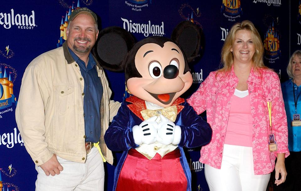 <p>The loving couple poses with Mickey Mouse during a trip to Disneyland in 2005. </p>