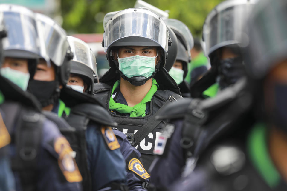 Riot police wearing face masks with their riot gear stand by during a pro-democracy demonstration in Bangkok, Thailand, Thursday, June 24, 2021. Pro-democracy demonstrators have taken to the streets of Thailand's capital again, marking the 89th anniversary of the overthrow of the country's absolute monarchy by renewing their demands that the government step down, the constitution be amended and the monarchy become more accountable. (AP Photo/Wason Wanichakorn)