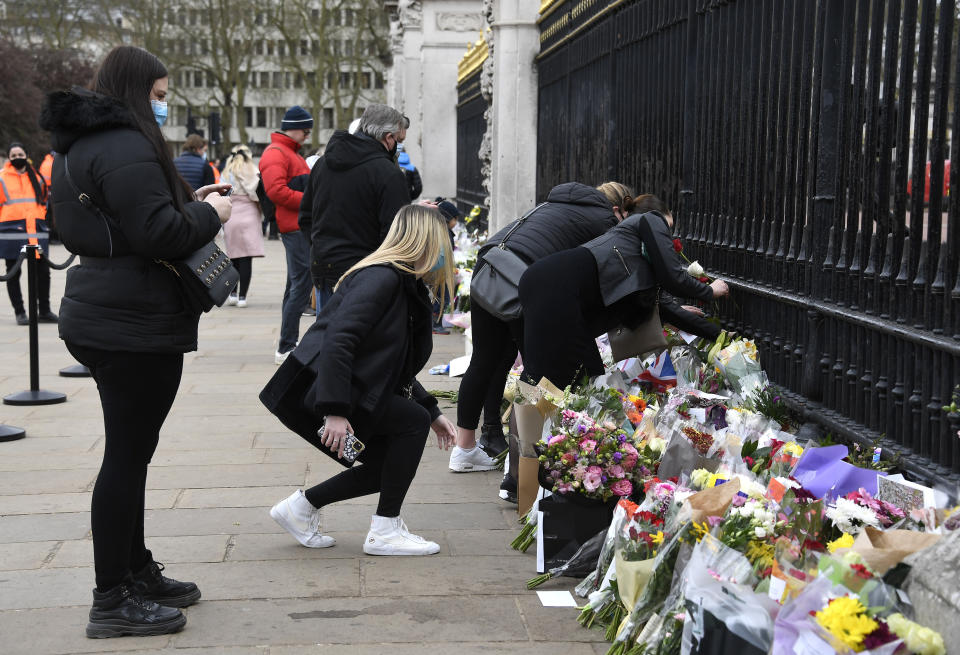 People leave flowers outside the gates of Buckingham Palace in London, a day after the death of Britain's Prince Philip, Saturday, April 10, 2021. Britain's Prince Philip, the irascible and tough-minded husband of Queen Elizabeth II who spent more than seven decades supporting his wife in a role that mostly defined his life, died on Friday. (AP Photo/Alberto Pezzali)