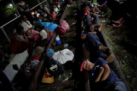 Honduran migrants, part of a caravan trying to reach the U.S., rest on the bridge that connects Mexico and Guatemala in Ciudad Hidalgo