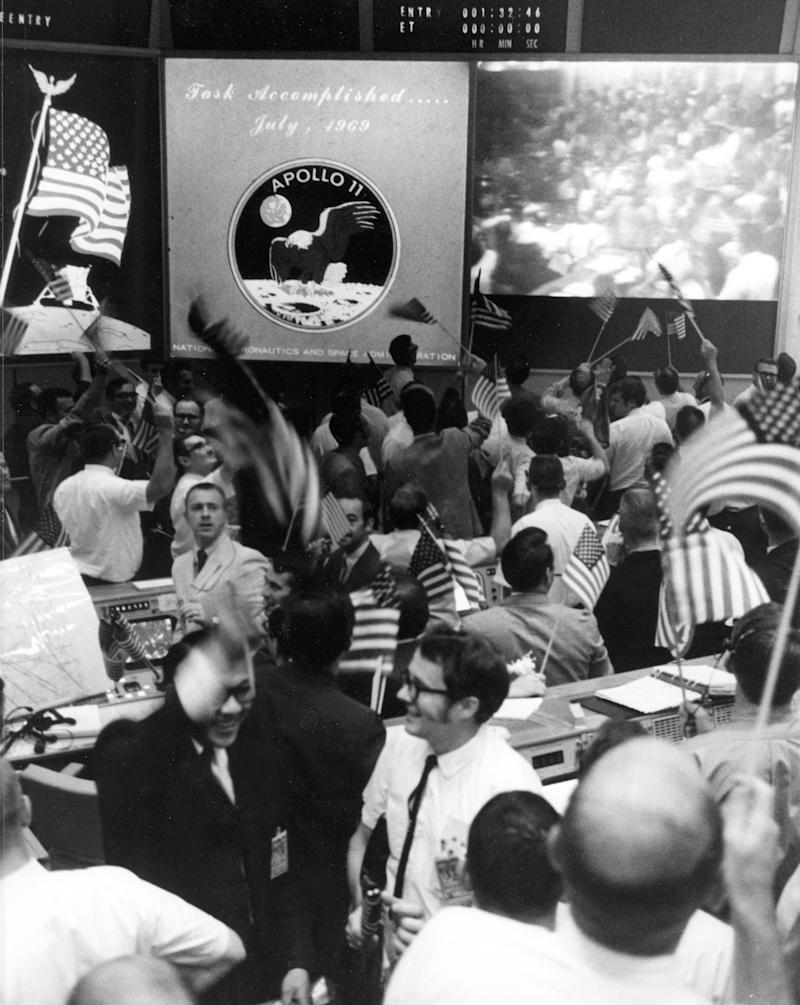 Overall view of the Mission Operations Control Room in the Mission Control Center, Building 30, Manned Spacecraft Center, showing the flight controllers celebrating the successful conclusion of the Apollo 11 lunar landing mission. | Bettmann/Corbis/Getty Images