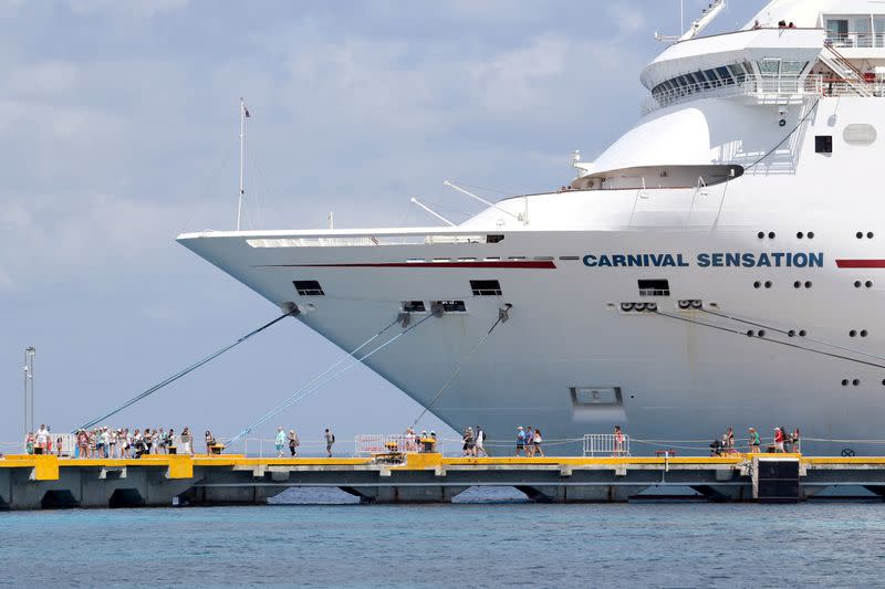 FILE PHOTO: Passengers of the Carnival Sensation, operated by Carnival Cruise Line, are seen next to the docked cruise ship in Cozumel