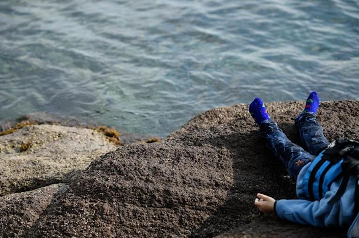 The body of a child who drowned when a boat sank in the Aegean Sea, is washed up on a beach in the Bademli district of Canakkale, on January 30, 2016 (AFP Photo/Ozan Kose)