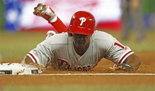 Philadelphia Philles' Jimmy Rollins dives back to first during the first inning of a baseball game against the Miami Marlins in Miami, Friday, June 29 2012 . (AP Photo/J Pat Carter)